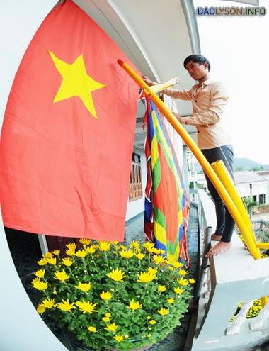 Người dân sửa soạn cờ tổ quốc, cờ phướn... chuẩn bị dựng cây nêu trong ngày 30 Tết ở huyện đảo Lý Sơn