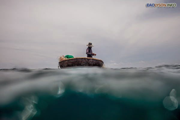 Một ngư dân trên một chiếc thuyền nhỏ giống như tách trà, được buộc vào một chiếc tàu lớn hơn, ở ngoài khơi bờ biển của đảo Lý Sơn. Căng thẳng với Trung Quốc buộc các ngư dân Việt Nam đánh bắt gần bờ, điều này đã làm cạn kiệt đáng kể nghề đánh cá ven biển.