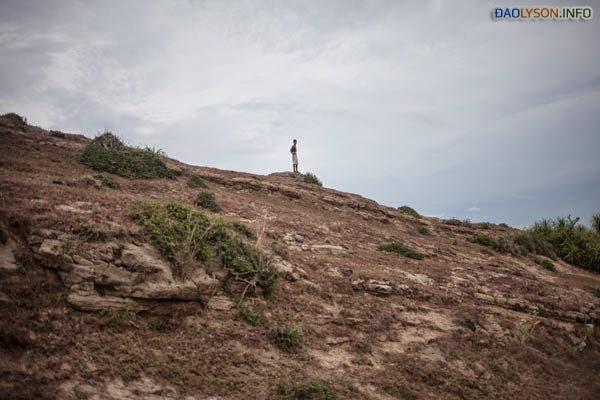 Một người đàn ông trèo lên một tảng đá để nhìn rõ hơn đàn gia súc nhỏ của mình đang chăn thả bên dưới
