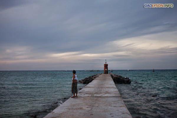 Một người đàn ông đi dọc cầu tàu và nhìn ra biển. Các cuộc tấn công của Trung Quốc vào các tàu đánh cá Lý Sơn đã làm cho tương lai của các ngư dân truyền thống trên hòn đảo bất định.