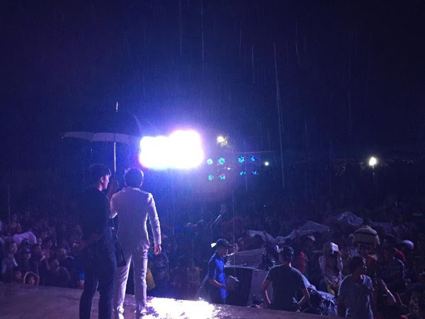 Nam ca sĩ nhiệt tình biểu diễn dưới mưa trước khi ban tổ chức mang dù ra che cho mình