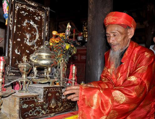 Ông Nguyễn Của (77 tuổi) đảm nhiệm ông Cả làng, rót rượu lên bàn thờ tổ tiên thầm báo lễ cầu an cho dân làng bắt đầu