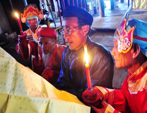 """Giây phút thiêng liêng nhất củalễ cầu an là lúc dâng sớ, ngoài ông Cả làng, thầy đồ đọc sớ của làng, hai """"ông đèn"""" cầm nến quỳ hầu hai bên soi rõ chữ trên sớ"""