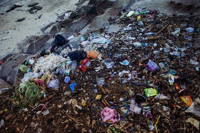 Chai nhựa, vỏ kẹo, hộp sữa, bao rác nằm chất đống trên bãi cát.