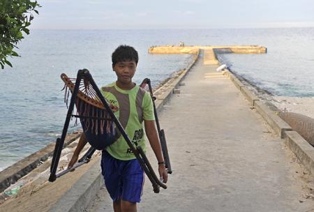 Một cậu trai vác võng xếp từ cảng về.