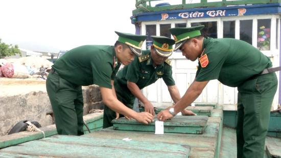 Cán bộ, chiến sĩ Đồn BP Lý Sơn niêm phong tang vật vi phạm trên tàu ông Nguyễn Ngọc Nhiên. Ảnh: Văn Tánh
