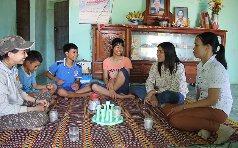 Bốn chị em Vũ cười tươi khi nghe cô Linh và giáo viên Trường THCS An Vĩnh pha trò bằng những câu chuyện vui - Ảnh: Trần Mai