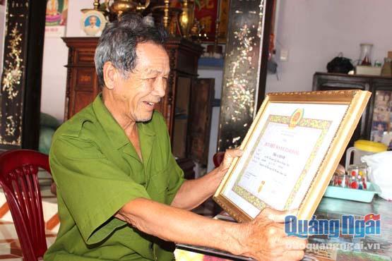 Ông Trần Chánh rạng rỡ bên tấm bằng khen do Đảng và Nhà nước trao tặng.