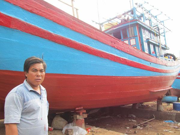 Ngư dân triệu đô Nguyễn Gia Viên bên con tàu đang được đưa lên đà sơn sửa. Ảnh: Nam Cường