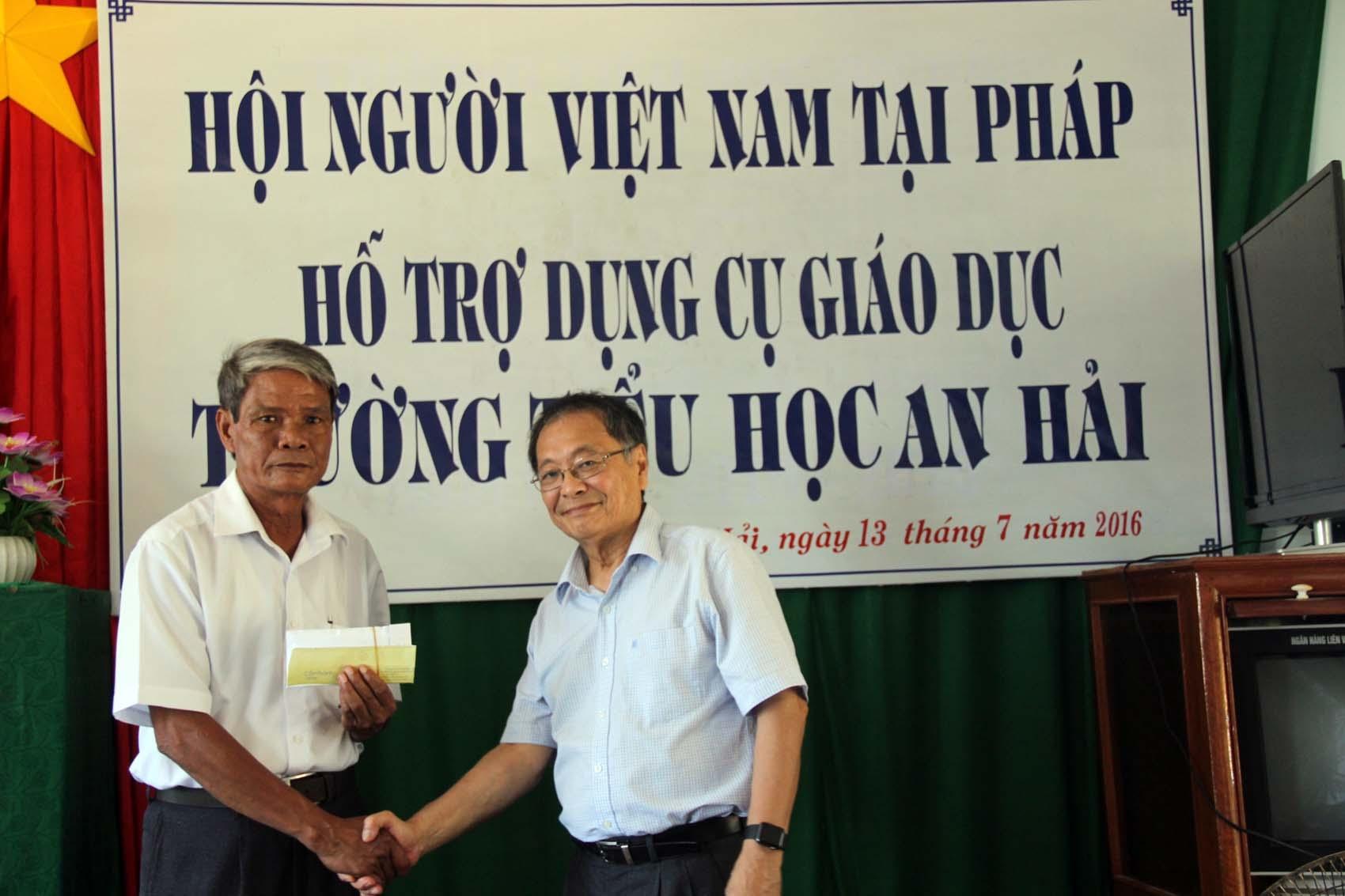 Đại diện Hội người Việt Nam tại Pháp (bên phải) hỗ trợ kinh phí mua sắm trang thiết bị và dụng cụ học tập cho nhà trường.