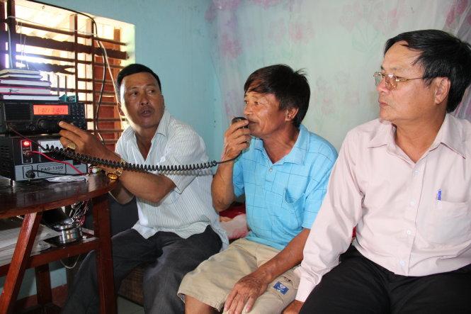 Ông Hùng (bìa phải) ngồi ngóng tin cùng người nhà ngư dân đang đánh bắt ở Hoàng Sa