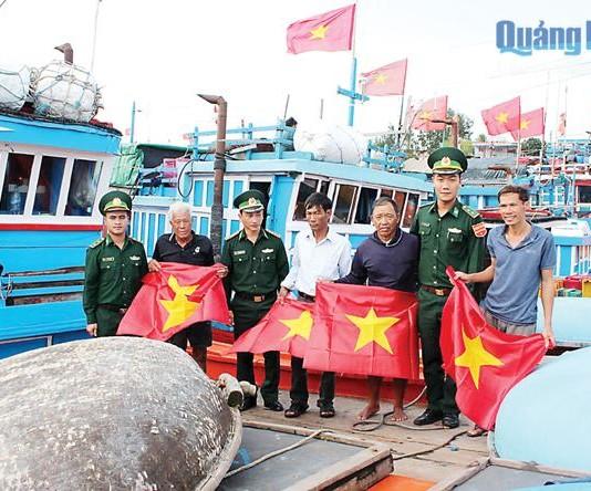 Cán bộ, chiến sĩ Đồn Biên phòng Lý Sơn tặng cờ Tổ quốc cho ngư dân khai trong chuyến biển đầu năm. ẢNH: K.TOÀN
