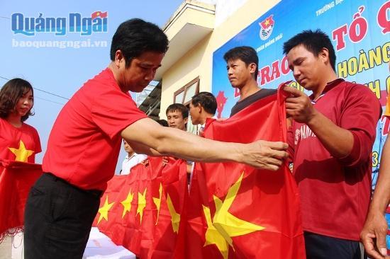 Đại diện Trường Đại học sư phạm Huế trao cờ tổ quốc cho ngư dân Lý Sơn.