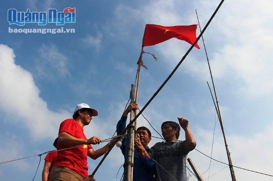 Đại diện Tỉnh Đoàn cùng Trường Đại học Sư phạm Huế gắn cờ Tổ quốc trên thuyền ngư dân.