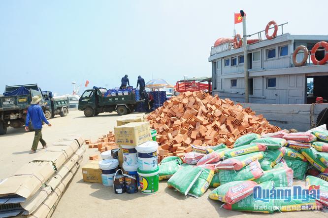 Vật liệu xây dựng được bốc dỡ từ sà lan lên cầu cảng Lý Sơn.