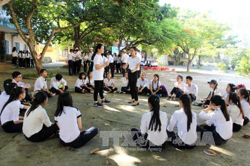 Tình nguyện viên đang trao đổi trực tiếp với học sinh. Ảnh: Phước Ngọc/TTXVN