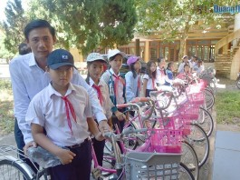 Đại diện Công ty Chín Nghĩa trao tặng xe đạp cho các em học sinh