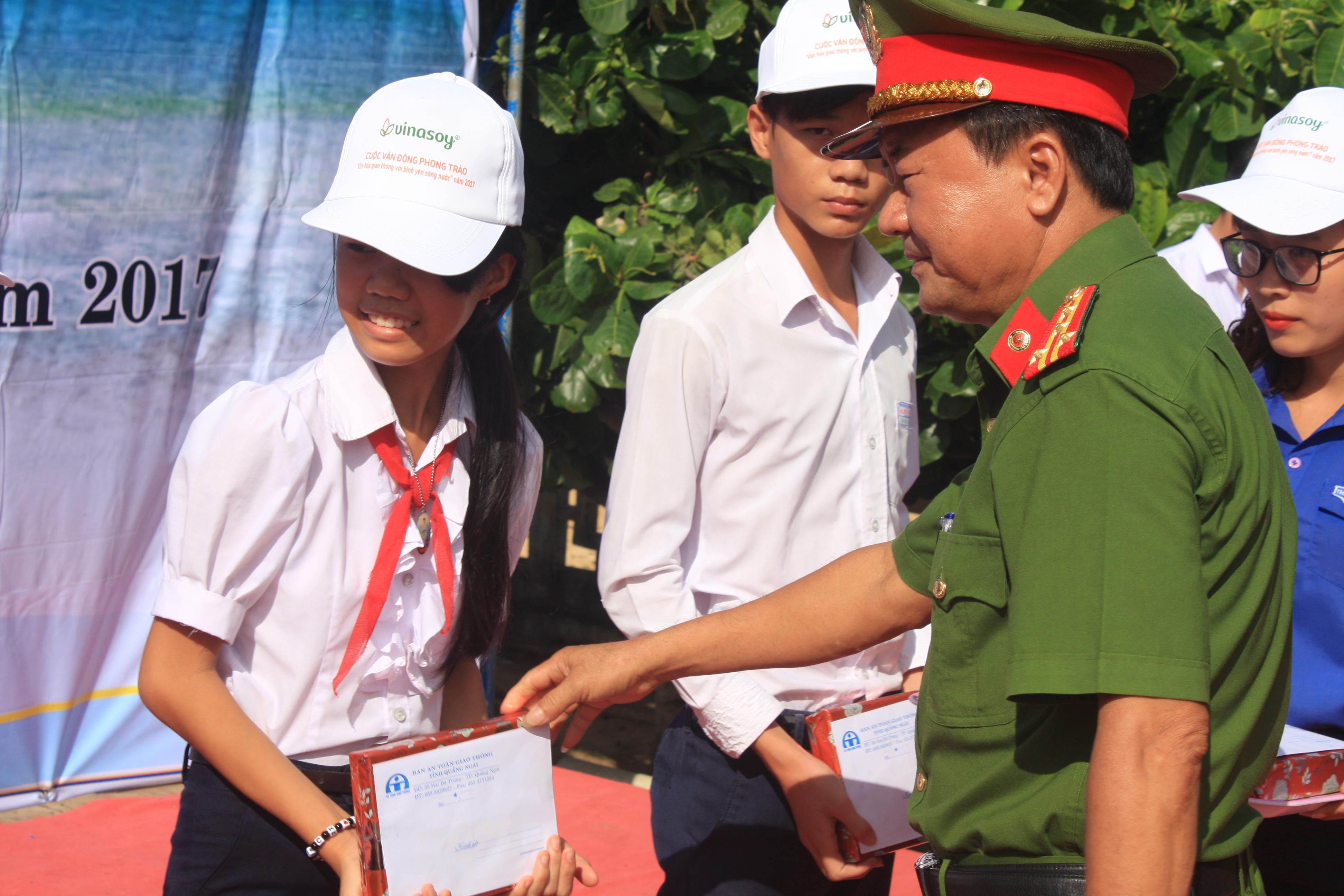 Đại tá Đặng Văn Nam, Phó Giám đốc công an tỉnh Quảng Ngãi kiêm Phó ban ATGT tỉnh trao quà cho học sinh.