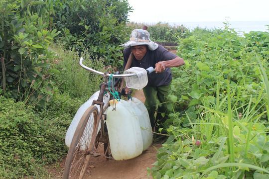 Ngày nào cũng vậy, ông Dương Kiên hì hục với 4 can nước đầy từ giếng cổ