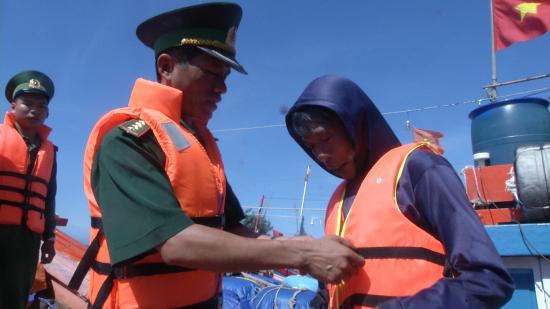 Cán bộ Đồn BP Lý Sơn hướng dẫn ngư dân mặc áo phao. Ảnh: Văn Tánh
