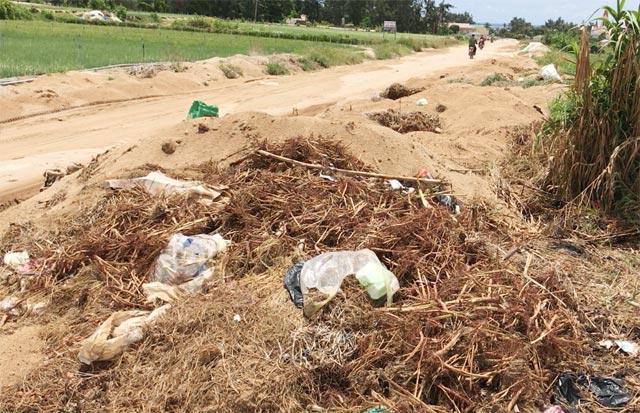 Một tuyến đường giao thông trên đảo bị đất thải và rác nông nghiệp thu hẹp