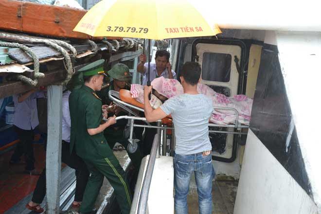 Lực lượng biên phòng hỗ trợ đưa sản phụ Thu từ tàu cao tốc ở cảng Sa Kỳ lên xe cấp cứu về Bệnh viện đa khoa Quảng Ngãi sinh nở.