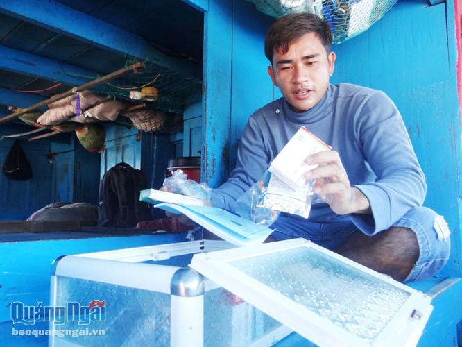Ngư dân Huỳnh Văn Thư kiểm tra tủ thuốc trên tàu cá của mình.