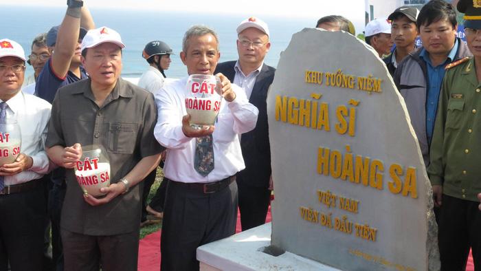 """Nâng niu những chiếc bình đựng cát Hoàng Sa đổ vào chân viên đá đầu tiên tại lễ khởi công """"Khu tưởng niệm nghĩa sĩ Hoàng Sa"""" ngày 17-1-2016"""