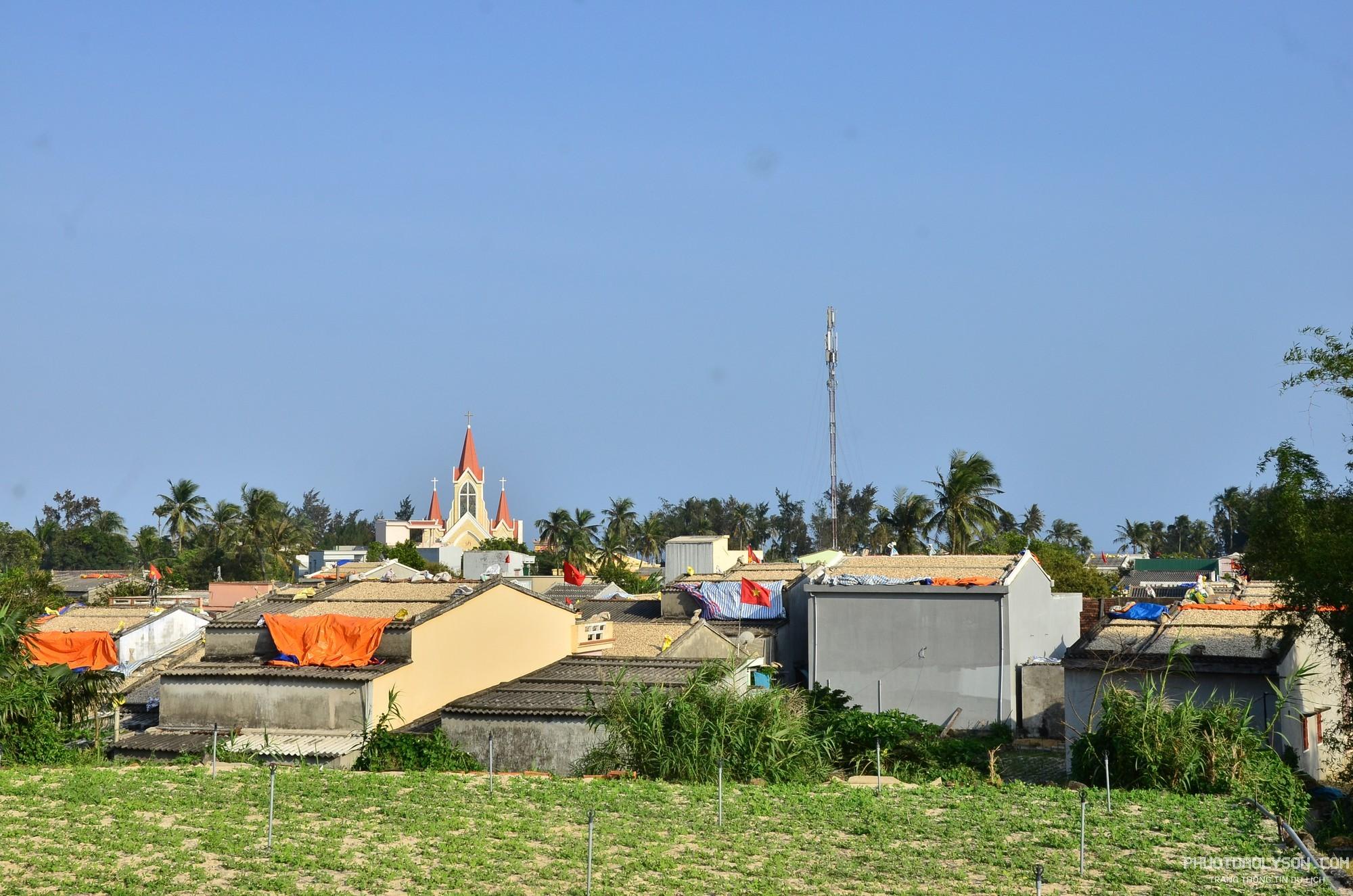 """Không chỉ ông Quảng, hàng trăm hộ dân khác cũng mang tỏi lên mái nhà để phơi tạo nên khung cảnh đặc trưng của """"vương quốc tỏi"""" Lý Sơn"""