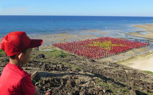 Hơn 3.000 người tạo hình cờ Tổ Quốc và hát Quốc ca tại bãi biển Hang Câu, huyện Lý Sơn, tỉnh Quảng Ngãi.