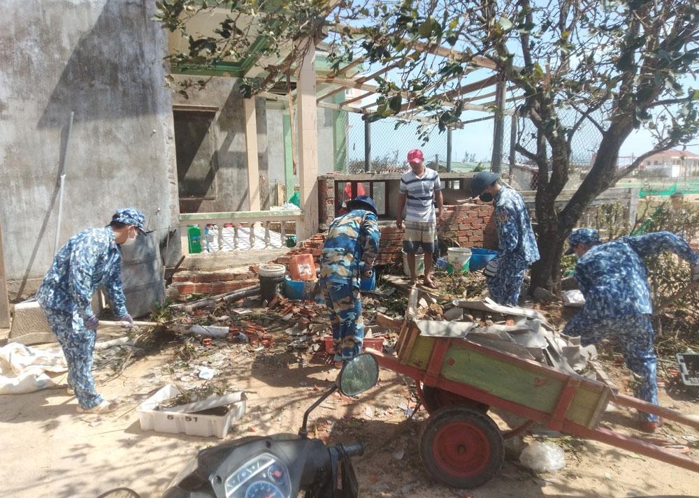 Cán bộ, chiến sĩ Trạm 2 Cảnh sát biển dọn dẹp nhà cửa giúp dân huyện đảo Lý Sơn khắc phục hậu quả sau bão số 9