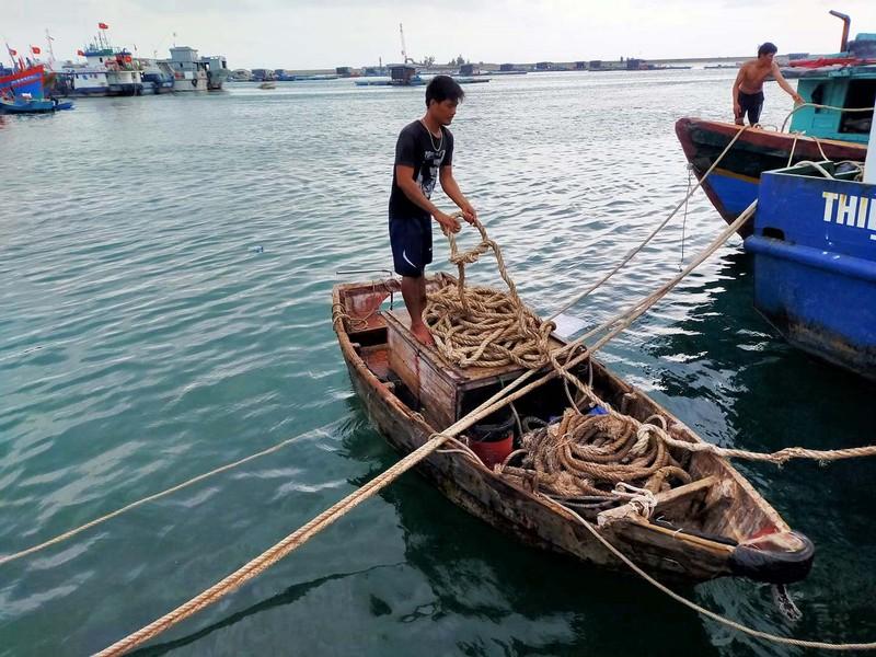 Ngư dân dùng dây thừng ràng buộc chắn chắn các thuyền tại bến neo đậu ở huyện đảo Lý Sơn.