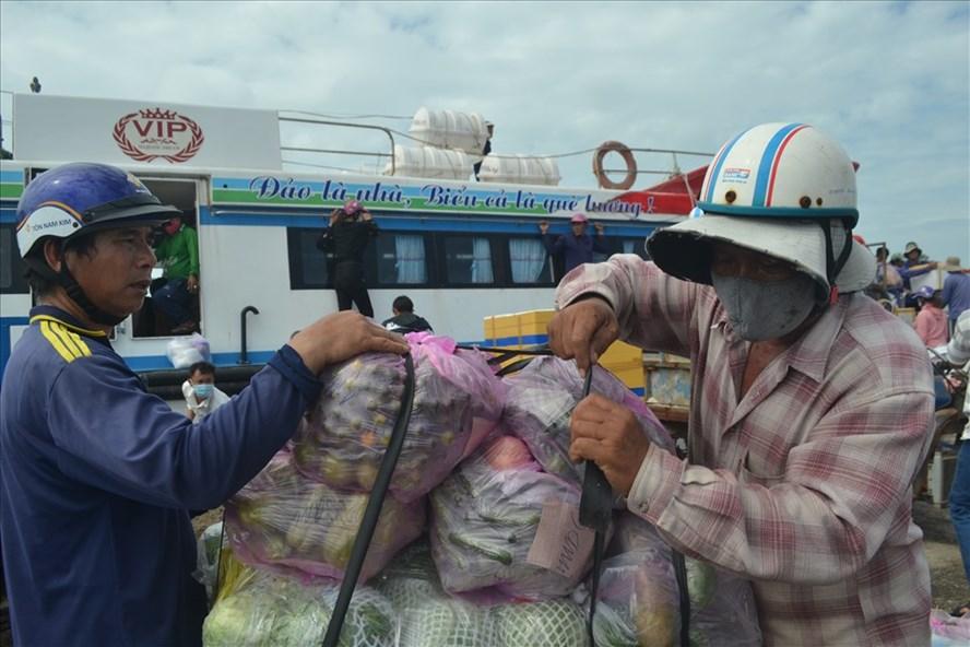 Người dân tiếp nhận nhu yếu phẩm từ đất liền gửi ra đảo để bổ sung nguồn thực phẩm thiết yếu đang bị thiếu hụt vì biển động kéo dài.