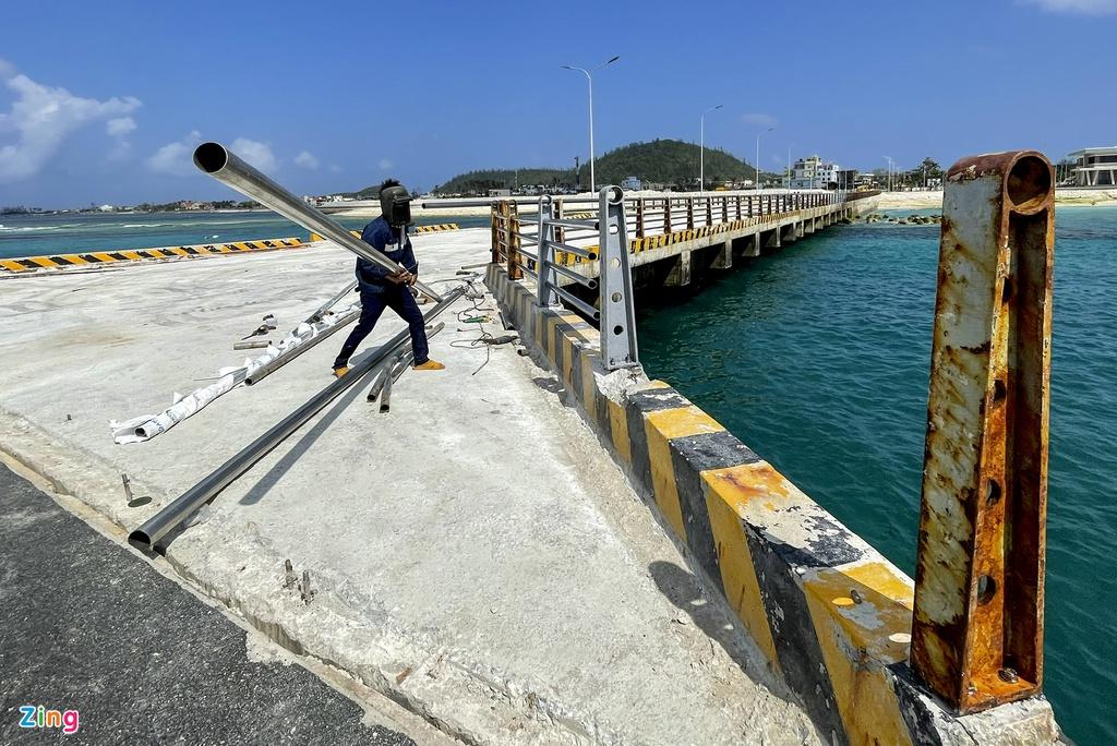 Những ngày này, chủ đầu tư phối hợp với các nhà thầu huy động phương tiện, nhân lực khắc phục các hạng mục hư hỏng. Trong ảnh, công nhân thay mới lan can cầu dẫn cảng Bến Đình sau khi bị sóng lớn đánh sập.